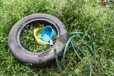 Standing water trapped in tire and containers in dirty environment breed mosquito Stok Fotoğraf - 105748933