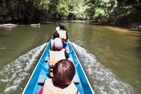 Tourists riding long boat on Merlinau river to Wind and Clear Water caves at Mulu National Park, Sarawak