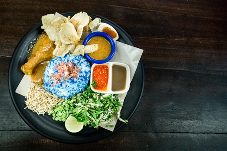 Nasi Kerabu with chicken and cordiments is popular traditional Malay food in Malaysia