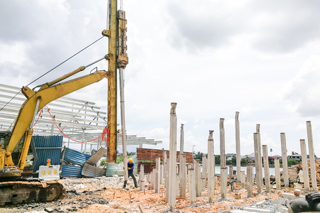 Worker carrying out ground piling work at construction site with heavy machinery Archivio Fotografico