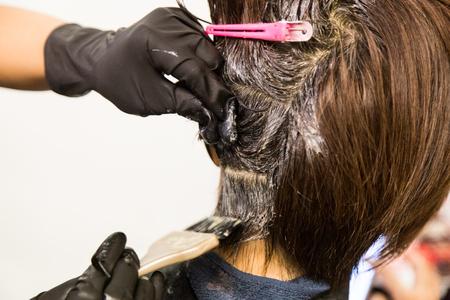 Closeup of hair dresser applying chemical color dye onto hair of customer in salon