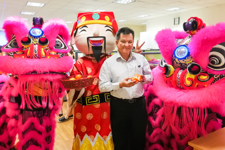 Chinese business manager posing with two lions in office after dance performance that believe to bring prosperity and good luck.