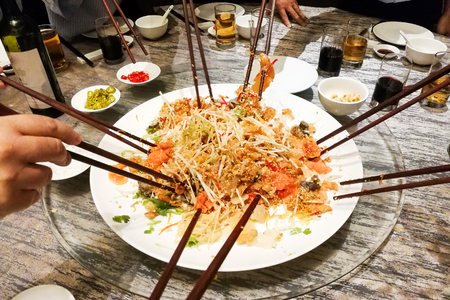 People tossing yee sang or yusheng during Chinese New Year , traditional practice in Malaysia and Singapore for luck and prosperity