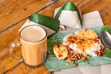 Simple banana leaf nasi lemak and teh tarik breakfast, popular breakfast in Malaysia Stock Photo