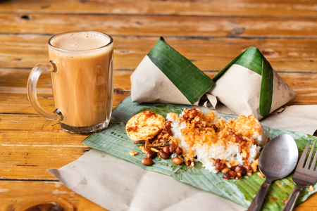 Simple banana leaf nasi lemak and teh tarik breakfast, popular breakfast in Malaysia Stock fotó