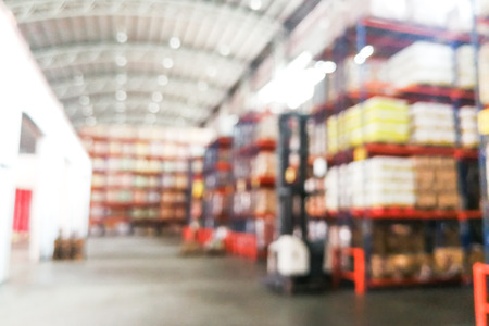 Defocused warehouse racks with cartons boxes as background resources