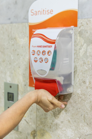 Person dispensing disinfectant sanitizer liquid onto hand at public amenities or hygienic living