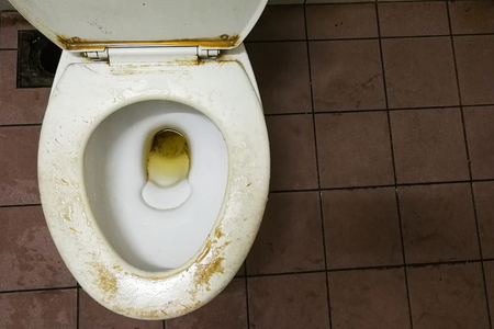Dirty smelly public toilet bowl with stain and limescale