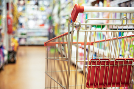 Shopping trolley cart against modern supermarket aisle blurred background
