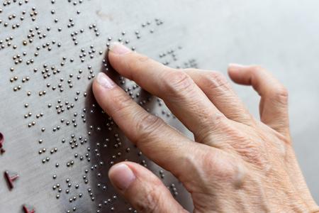Lettura del dito braille tattile sulla bacheca del parco pubblico a Hong Kong