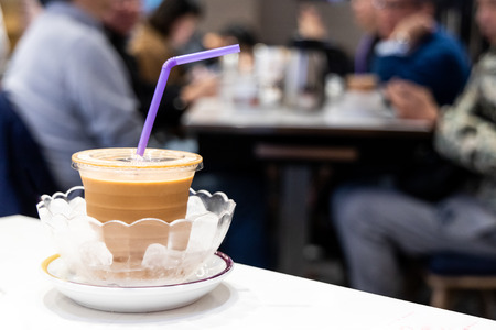 Cold silky smooth milk tea infused with ice in bowl, popular drinks served in restaurants in Hong Kong 免版税图像