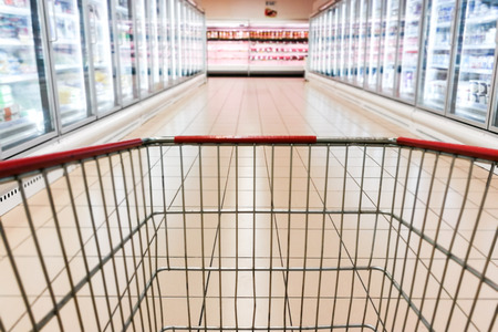 Perspective view of shopping trolley cart with modern supermarket chiller frozen aisle blurred background Stock Photo