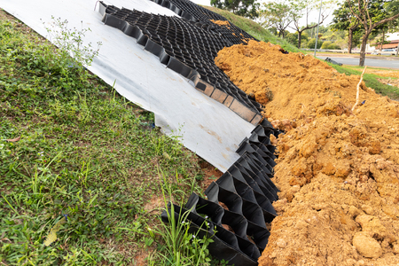 Close-up on slope erosion control materials with grids, sheets and earth on steep slope