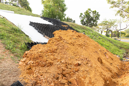 Slope erosion control materials with grids, sheets and earth on steep slope to manage landslide Reklamní fotografie