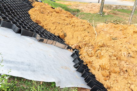 Close-up on slope erosion control materials with grids, sheets and earth on steep slope to manage landslide