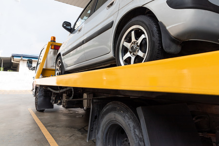 Broken down car on flatbed tow truck being transported to garage workshop for repair Stock Photo