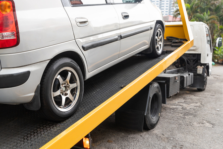 Broken down car being towed onto flatbed tow truck with cable for repair at workshop garage Фото со стока - 123093318