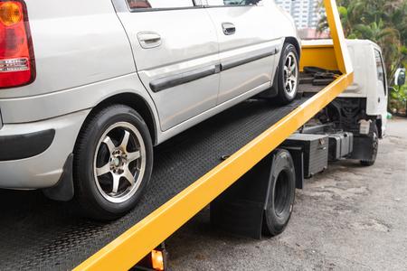 Kapotte auto wordt gesleept op flatbed sleepwagen met kabel voor reparatie in werkplaatsgarage Stockfoto