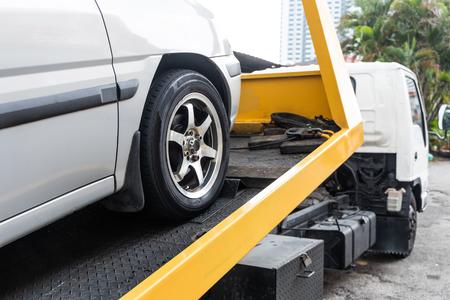 작업장 차고에서 수리를 위해 케이블이 있는 평판 견인 트럭으로 견인되는 고장난 자동차