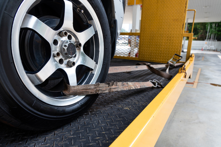 Broken down car tied with security strap on flatbed tow truck for transport to workshop garage to repair.
