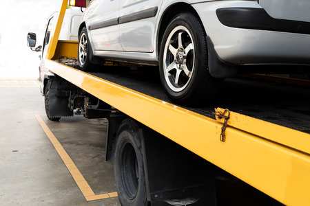 Aufgeschlüsseltes Auto auf einem Tieflader-Abschleppwagen, der zur Reparatur in eine Garagenwerkstatt transportiert wird Standard-Bild