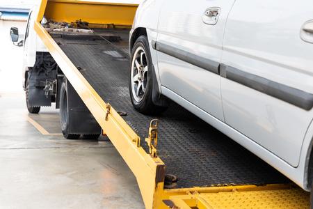 Kapotte auto wordt gesleept op flatbed sleepwagen met kabel voor reparatie in werkplaatsgarage