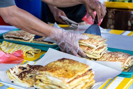 Seller preparing murtabak at street stall for iftar during muslim fasting month of Ramadan. Stock fotó