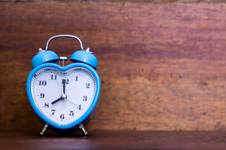 Heart shaped alarm clock on wooden background. Time is Eight O Clock Banco de Imagens