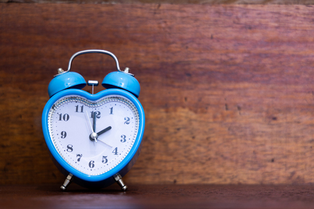 Heart shaped alarm clock on wooden background. Time is Two O Clock Banco de Imagens