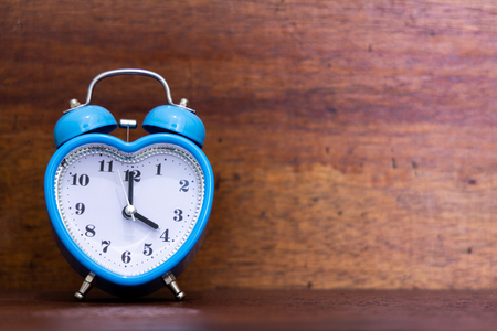 Heart shaped alarm clock on wooden background. Time is Four O Clock