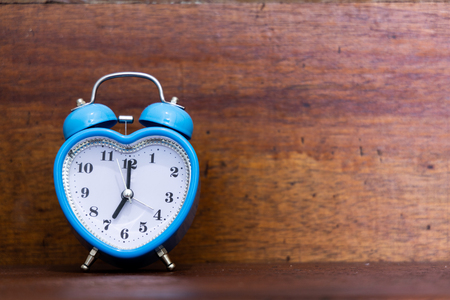 Heart shaped alarm clock on wooden background. Time is Seven O Clock Banco de Imagens