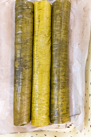 Thee rolls of lemang, glutinous rice cooked in bamboo, popular during Hari Raya celebration in Malaysia Stock Photo