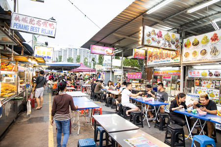 PENANG, JUNE 7, 2019: People dining at Gurney Drive hawker centre.  Gurney Drive offers variety of popular local delicacies and is popular among tourists.