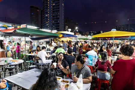 Penang, 7 czerwca 2019 r.: Ludzie jedzący w centrum handlowym Gurney Drive. Gurney Drive oferuje wiele popularnych lokalnych przysmaków i jest popularny wśród turystów.