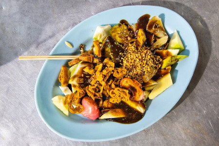 Popular Penang fruit rojak served with prawn paste and groundnuts, served on table