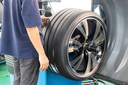 Reihe von Arbeitern, die Reifen mit Radauswuchtmaschinen in der Werkstatt auswuchten