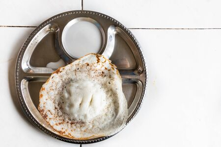 Apom or apam, traditional sweet Malaysia food of Indian origin, served on plate with coconut milk dip Stock Photo