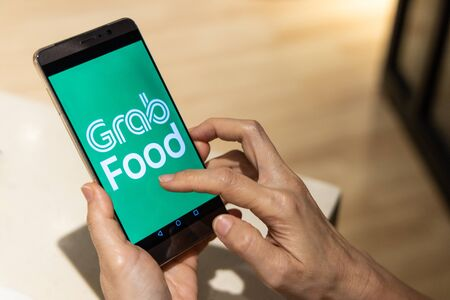 KUALA LUMPUR, MALESIA, 17 settembre 2019: Concettuale della persona che ordina cibo online tramite l'app Grabfood su smartphone. Grabfood è un servizio di consegna di cibo in più rapida crescita in Asia.