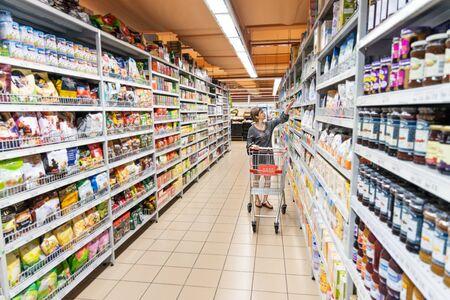 Reihe von asiatischen Frauen, die Lebensmittel im modernen Supermarkt einkaufen, mit Einkaufswagen, die Produkte auswählen