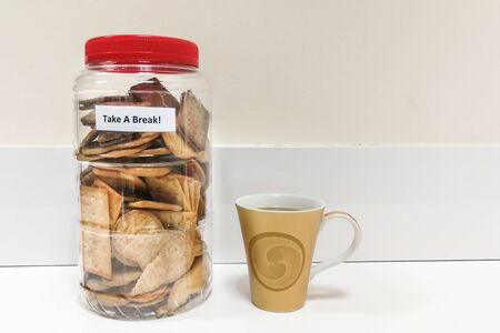 Biscuit in plastic jar with Take A Break word, at office pantry Foto de archivo