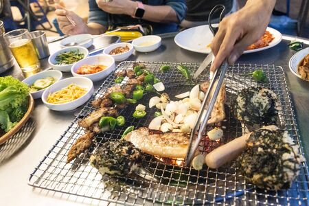 Closeup of Korean barbecue being grilled on hot charcoal stove along with other ingredients