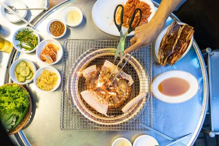 Overhead view of Korean barbecue being grilled on charcoal stove, with other dishes