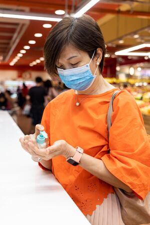 Closeup of Asian woman applying sanitizer onto hand for protection against infectious virus, bacteria and germs