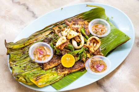 Grilled stingray fish fillet with spices on banana leaf and chili dips, popular Malaysia delicacy. Banque d'images