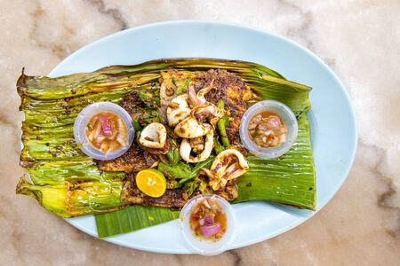 Grilled stingray fish fillet with spices on banana leaf and chili dips, popular Malaysia delicacy.