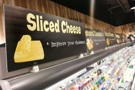 Cheese signage at supermarket refrigerated produce food section with defocused background