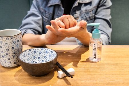 Series of person cleaning hands after spraying with disinfectant sanitizer before meal at dining table