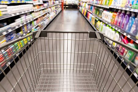 Shopping trolley cart moving in supermarket with motion blur aisle with grocery background Reklamní fotografie