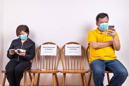 People with face mask seated in-between two chairs at public place, with Social Distancing, Do Not Sit signage to prevent spread of Covid-19 pandemic Standard-Bild