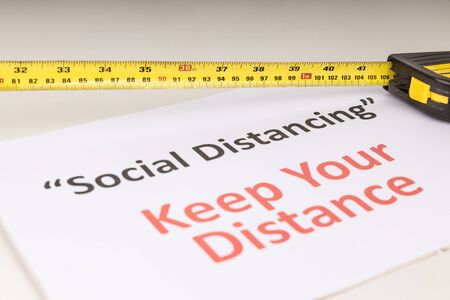 Social Distancing concept with measuring tape focused on 1 meter mark against Keep Your Distance placard